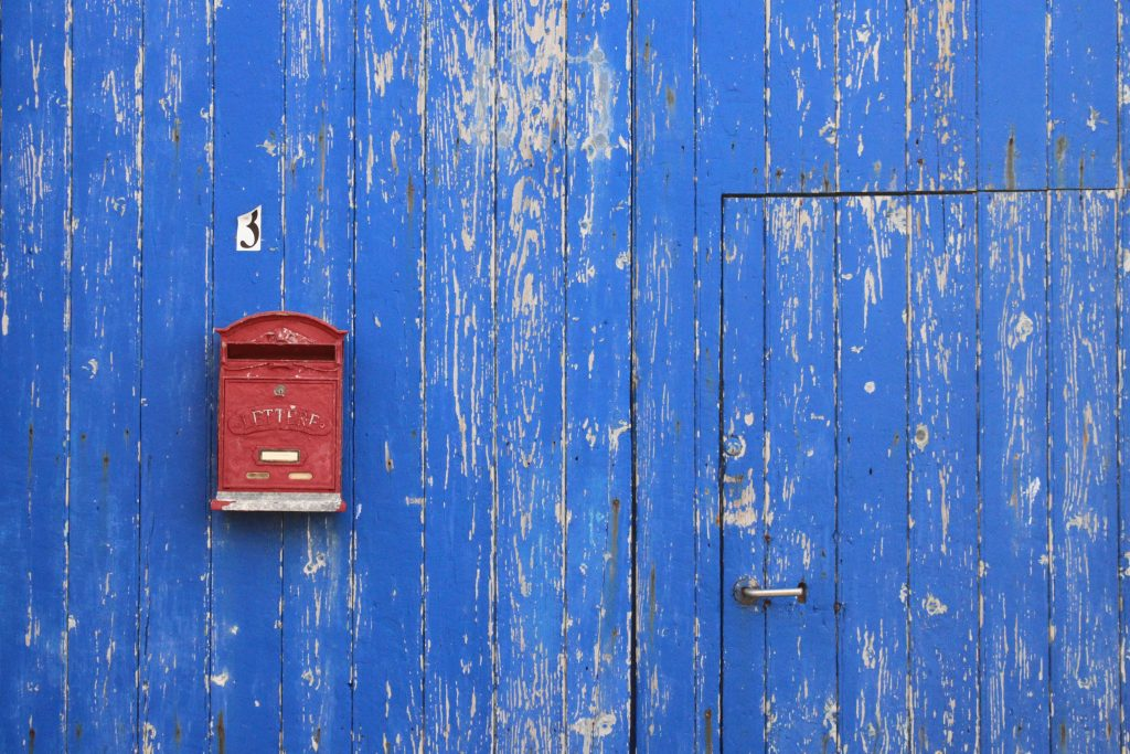 Distressed, blue barn with a door and a red mailbox.
