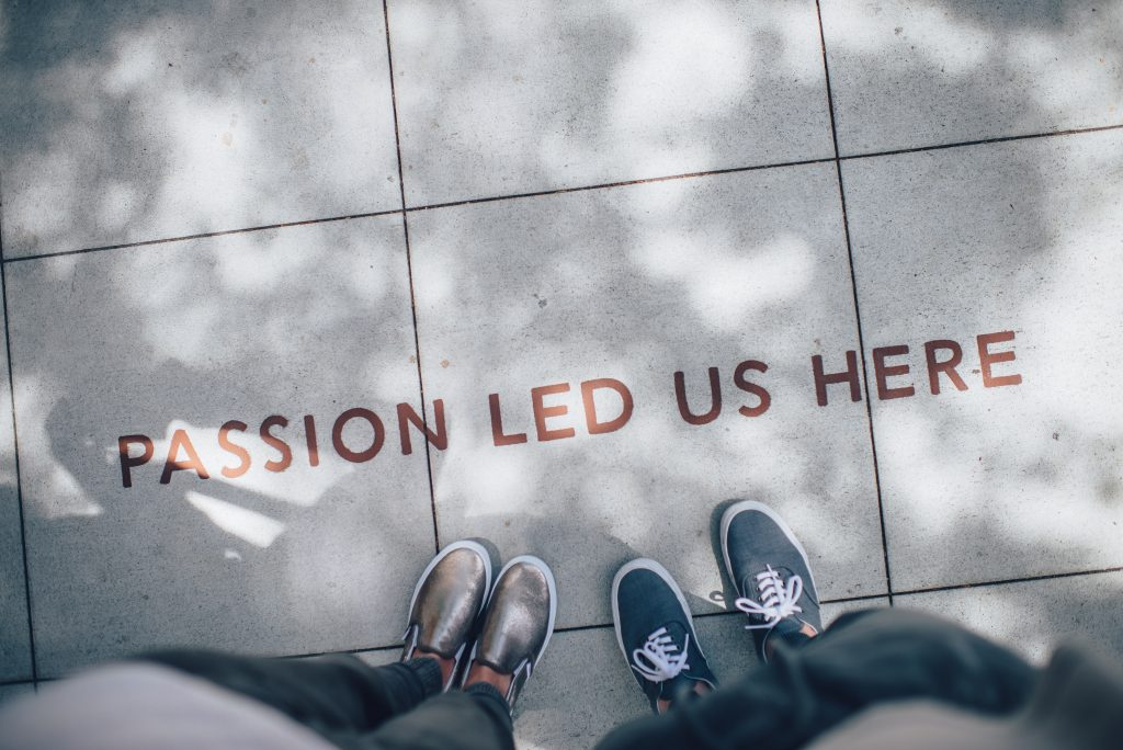 Two people looking down at a sidewalk with 'passion led us here' engraved on it.