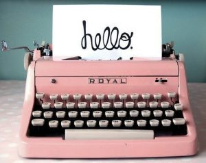 Pink Royal typewriter with paper that says 'hello'
