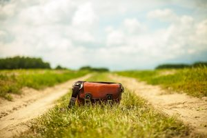 Leather messenger bag sitting in the middle of a dirt road looking toward the horizon.