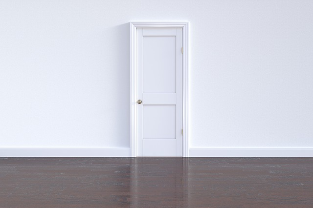 Looking over a dark brown wood floor at a white will with a white door.