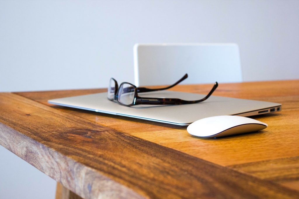 Laptop, glasses, computer mouse sitting on a wooden table