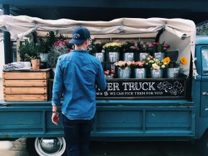 Person standing in front of a florist truck