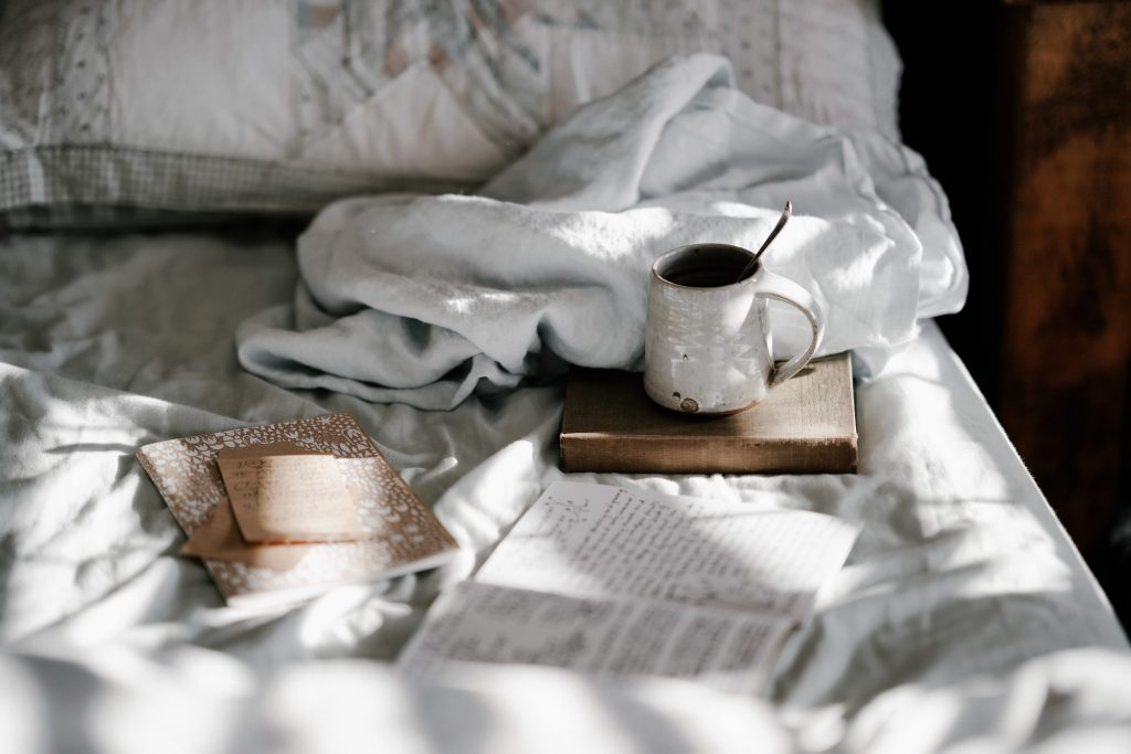 Cozy blanket on a bed with a few notebooks and a cup of tea.