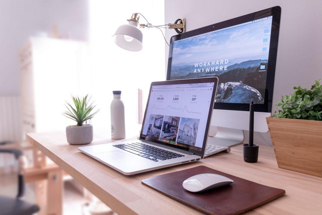 Laptop and desktop computer on work desk.